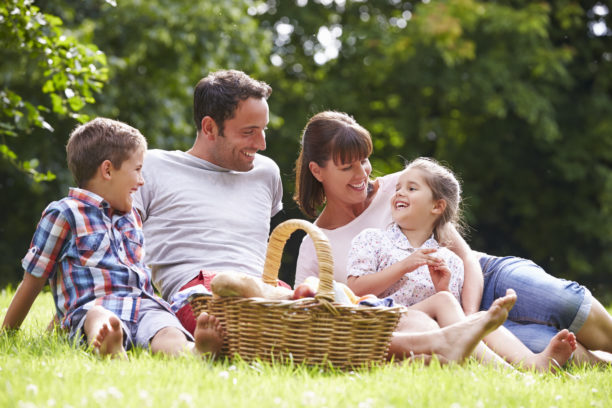 family laughing while enjoying a picnic