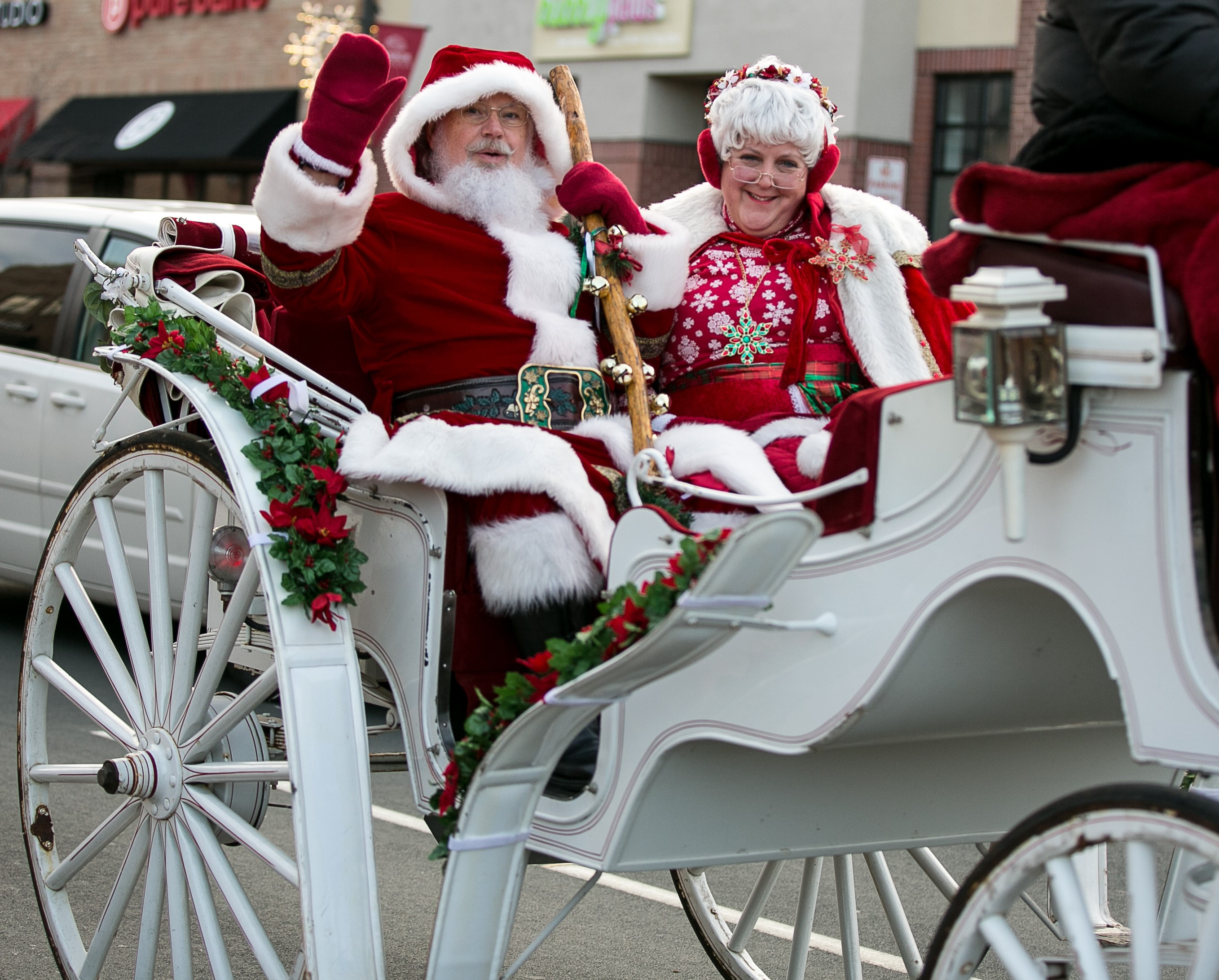 Mr. and Mrs. Claus waving to people