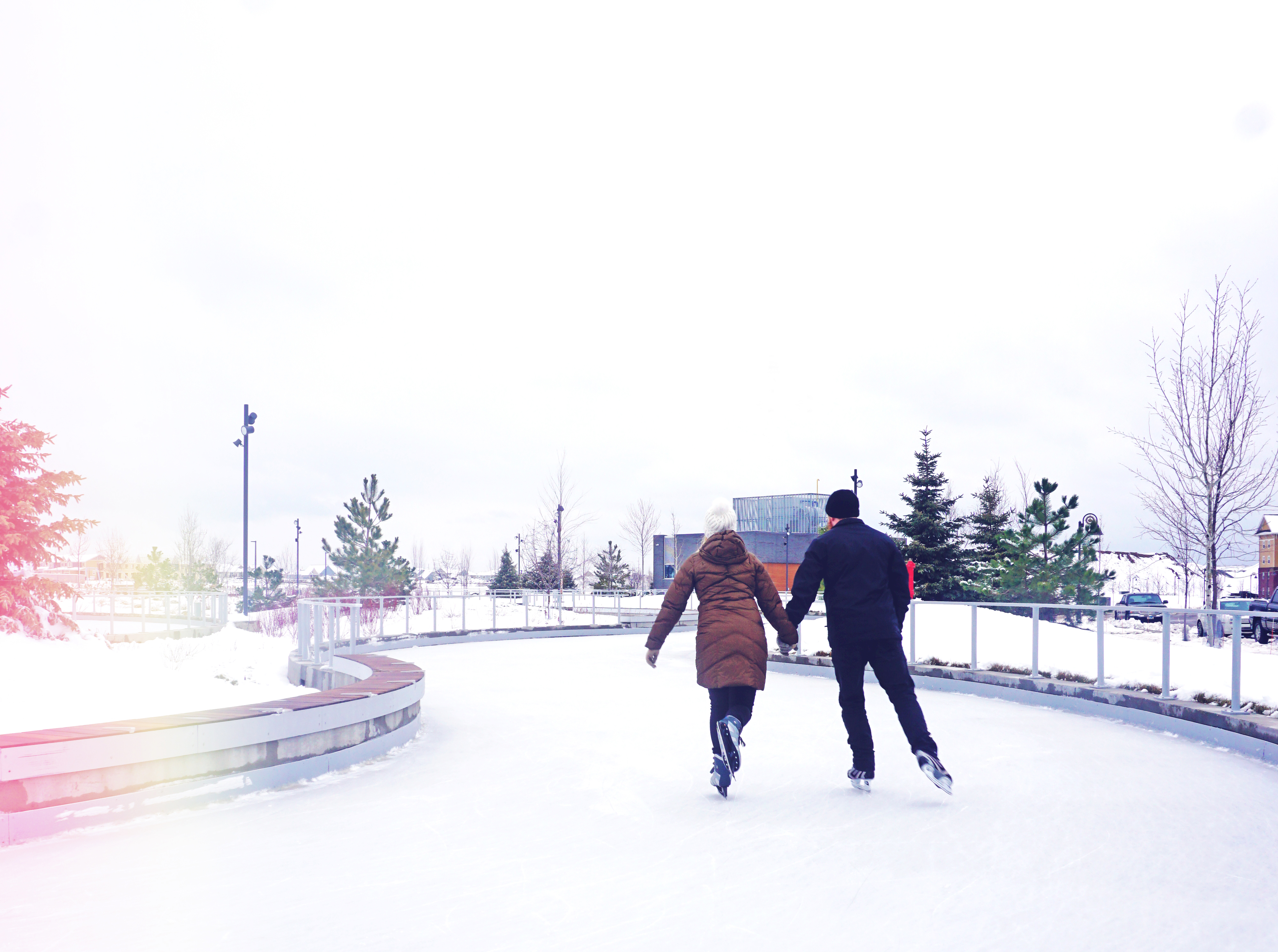 Couple holding hands while skating on ice trail