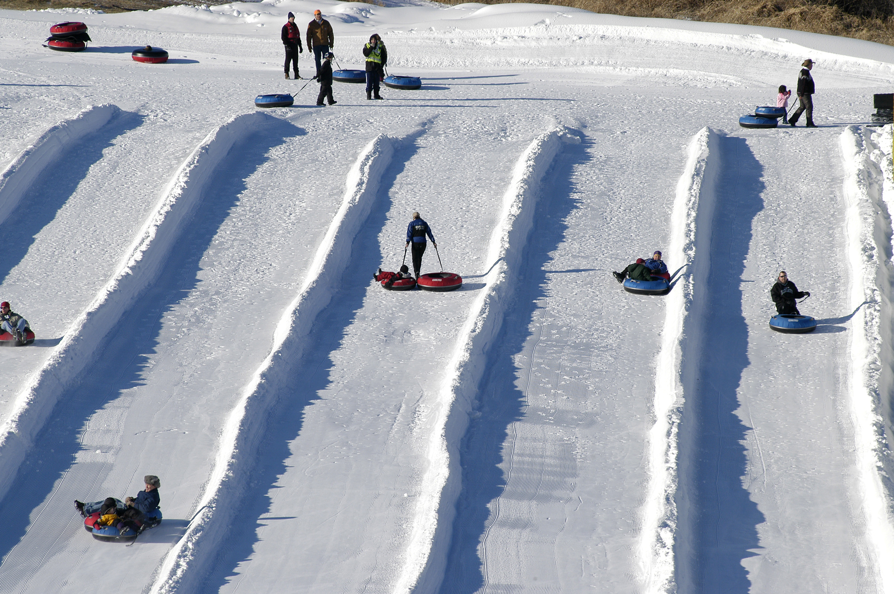 people tubing down large hill