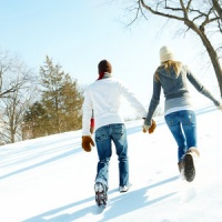 V-day couple wlaking up hill in snow